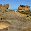 Sandstone rock on beach - Stock Photo