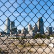 Stock Photo: City behind fence