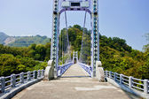 A suspension bridge across mountains — Stock Photo
