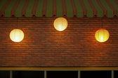 Brick wall with three illuminated lamps — Stock Photo