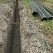 Plastic pipes in a ditch — Stock Photo