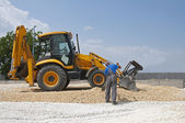 Worker and gravel excavator — Stock Photo