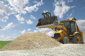 Excavator to a pile of rubble — Stock Photo