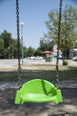 Empty green swing with chain — Stock Photo