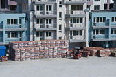 Pallets of bricks in front of new building — Stock Photo