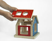 Boy hands and wood colorful house toy — Stock Photo