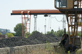 Crane and piles of coal — Stock Photo
