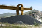 Asphalt pile and crane in quarry — Stock Photo