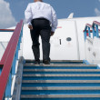 Stock Photo: Businessmwho climbs on plane