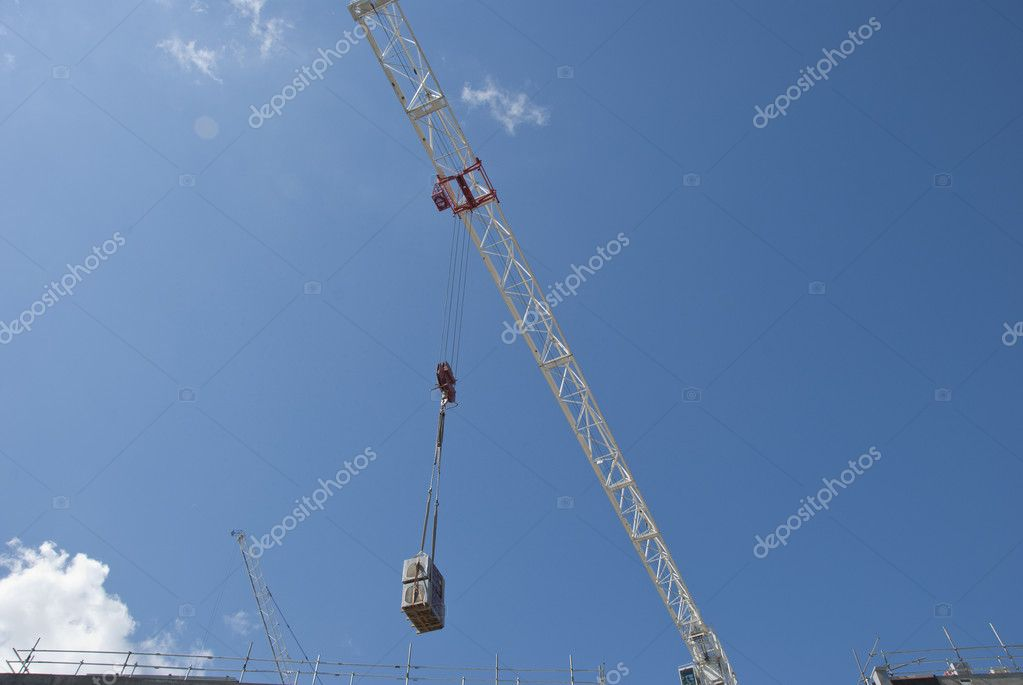 A White Tower Crane lifting an air conditioning unit on a consruction site — Stock Photo #6525917