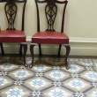 Upholstered Wooden Chair and Tessellated Tiles - Stock Photo