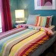 Vibrant blue and multi coloured bedroom - Stock Photo