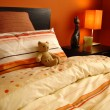 Stock Photo: Orange bedroom with teddy bear
