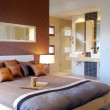 Modern bedroom with warm tones and ensuite bathroom - Stock Photo