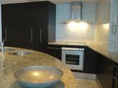 Spacious white open plan kitchen with breakfast bar — Stock Photo