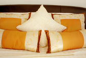 Orange cushions on the bed — Stockfoto