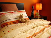 Orange bedroom with teddy bear — Stock Photo