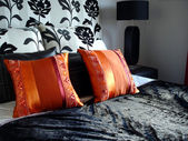 Modern bedroom luxurious black with orange red pillows — Stock Photo