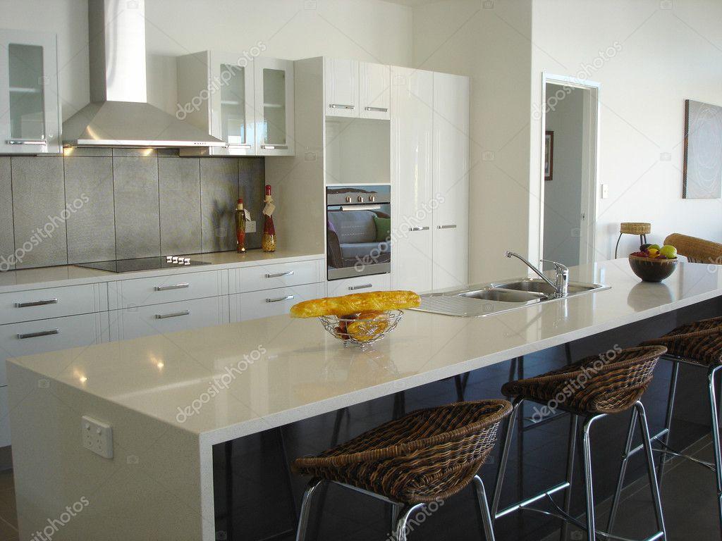 Spacious white open plan kitchen with breakfast bar