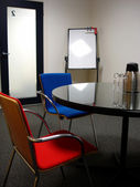 Business meeting room with bright red and blue modern chairs — Stock Photo