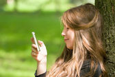 Attractive girl with phone in park — Stock Photo
