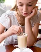 Woman is stirring coffee — Stock Photo