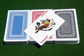 Joker over three decks of cards — Stock Photo