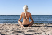 Blonde girl in a black bathing suit sits on the beach and meditate — Stock Photo
