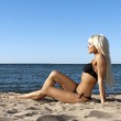 Blonde girl in a black bathing suit sitting on shore blue sea — Stock Photo