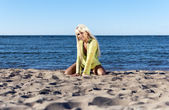 Blonde girl in a yellow tunic, sits near the sea on his knees — Stock Photo
