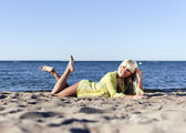Blonde girl in a yellow tunic lies near the sea on his knees — Stock Photo