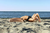 Blonde girl in a black bathing suit lying on the beach and meditate — Stock Photo