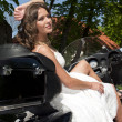 Beautiful young bride sitting on a motorcycle — Stock Photo