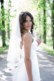 Young bride standing in an alley in the park — Stock Photo