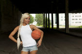 Beautiful blonde girl standing with basketball in the street — Stock Photo