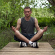 Man sitting in the lotus position and meditates — Stock Photo