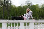 Chica rubia sentado sobre la barandilla — Foto de Stock