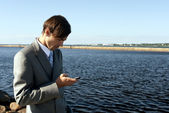 Man in a gray suit dials the phone against the sea — Stock Photo