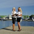 Two girls with the documents standing on the pier — Stock Photo