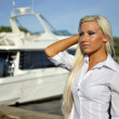 Stock Photo: Portrait of blonde girl in a white shirt against the boat