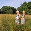 Stock Photo: Two girls in the grass near the forest