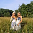Two girls in the grass near the forest — Stock Photo #6324311