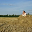 Girl in traditional Russian costume lying on a haystack — Stock Photo