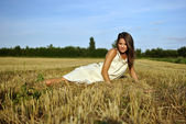 Nice girl in national dress sitting on a field in rural areas — Stock Photo
