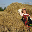 Girl in traditional Russian costume resting on a haystack — Stock Photo