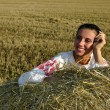 Stock Photo: Girl in traditional Russian costume lying on a haystack and smiling
