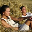 Two girls in traditional Russian costume resting on a haystack — Stock Photo