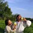 Two girls in traditional costume eating apples — Stock Photo #6640105