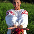Russian girl in traditional dress holding a strawberry in hand — Stock Photo