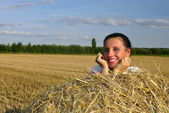 Girl in traditional Russian costume lying on a haystack and smiling — Stock Photo